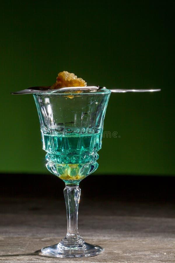 Açúcar ardente na colher no vidro do absinto imagens de stock