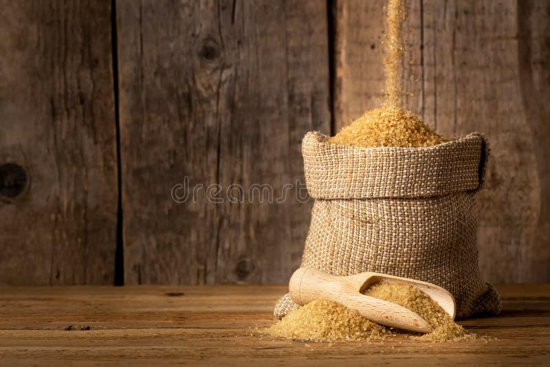 Açúcar de bastão de Brown no saco de serapilheira fotografia de stock