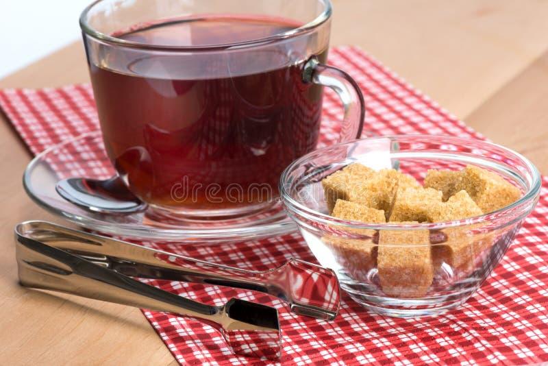 Açúcar de bastão de Brown e um copo do chá fotos de stock royalty free