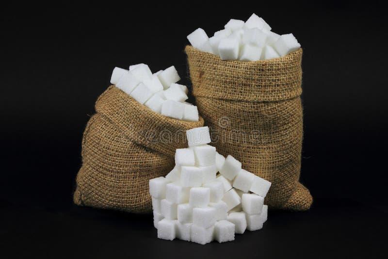 Açúcar de cubos em sacos de serapilheira sobre o preto. foto de stock