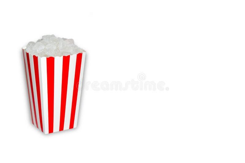 Açúcar escondido no foo, uma caixa da pipoca completamente de cubos cristal do açúcar no fundo branco com espaço da cópia imagem de stock