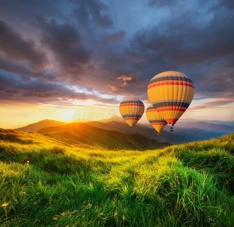 Aérez le ballon au-dessus des montagnes à l'heure d'été images libres de droits