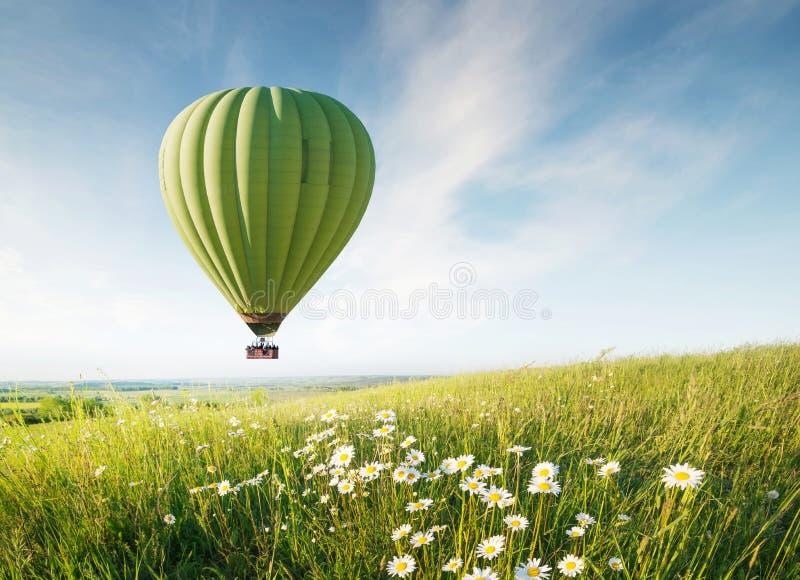 Aérez le ballon au-dessus du champ avec des fleurs à l'heure d'été photographie stock libre de droits