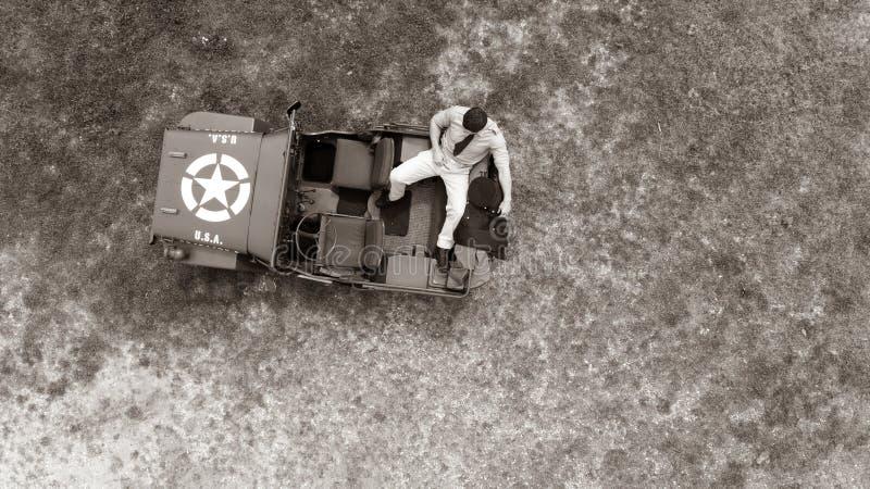 Aérien, bourdon, regardant vers le bas sur le dirigeant d'armée masculin dans l'uniforme se reposant dessus soutenez du véhicule  photos libres de droits