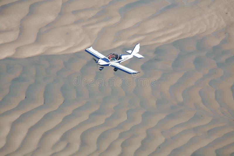 Aéronefs de vol au-dessus de sable image stock