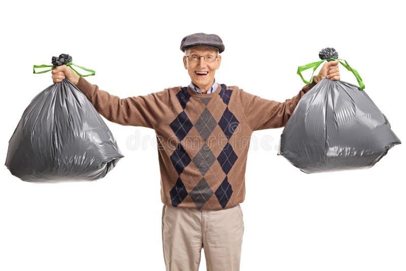 Aîné avec des sacs de déchets image libre de droits