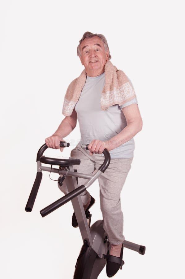 Aîné avec le vélo d'exercice d'isolement sur le blanc photographie stock libre de droits