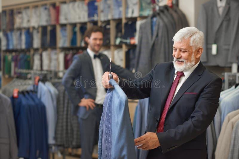 Aîné bel avec les cheveux gris choisissant les vêtements élégants image libre de droits