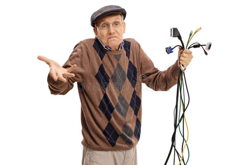 Aîné dérouté tenant différents types de câbles électroniques photographie stock libre de droits