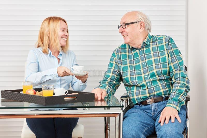 Aîné et jeune femme prenant le petit déjeuner à la maison photos stock