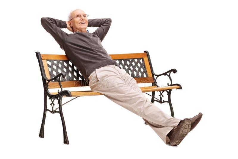 Aîné insouciant s'asseyant confortablement sur un banc images stock