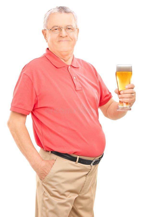 Aîné joyeux tenant une pinte de bière image libre de droits