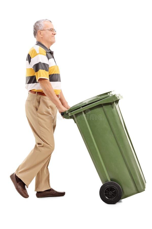 Aîné poussant une grande poubelle verte photographie stock