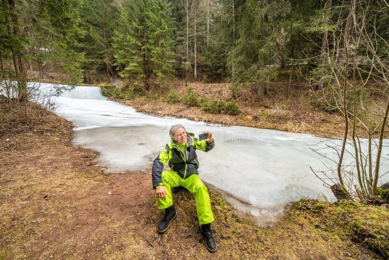 Aîné prenant un selfie près de la rivière congelée photos stock