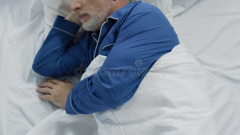Aîné se situant dans le lit, incapable de calmer vers le bas et tomber endormi, manque de confort photo libre de droits