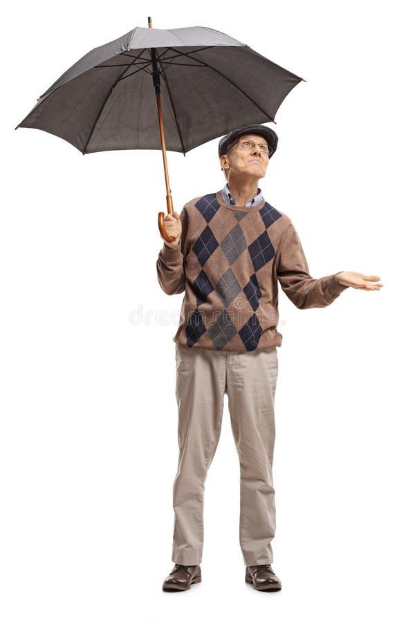 Aîné tenant un parapluie et vérifiant pour voir s'il pleut photographie stock libre de droits
