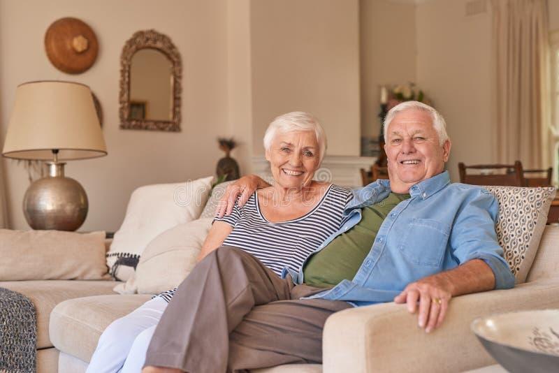 Aînés de sourire détendant sur leur sofa de salon photographie stock libre de droits