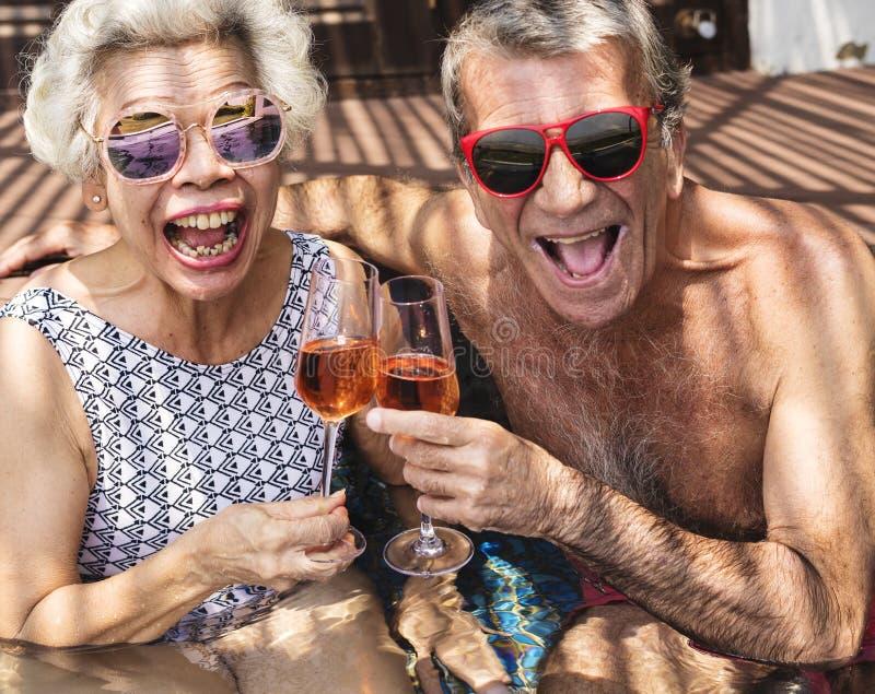 Aînés heureux buvant le prosecco dans la piscine photos libres de droits