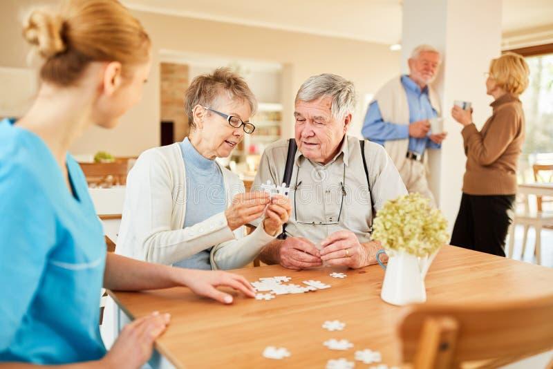 Aînés jouant le puzzle aux loisirs images stock