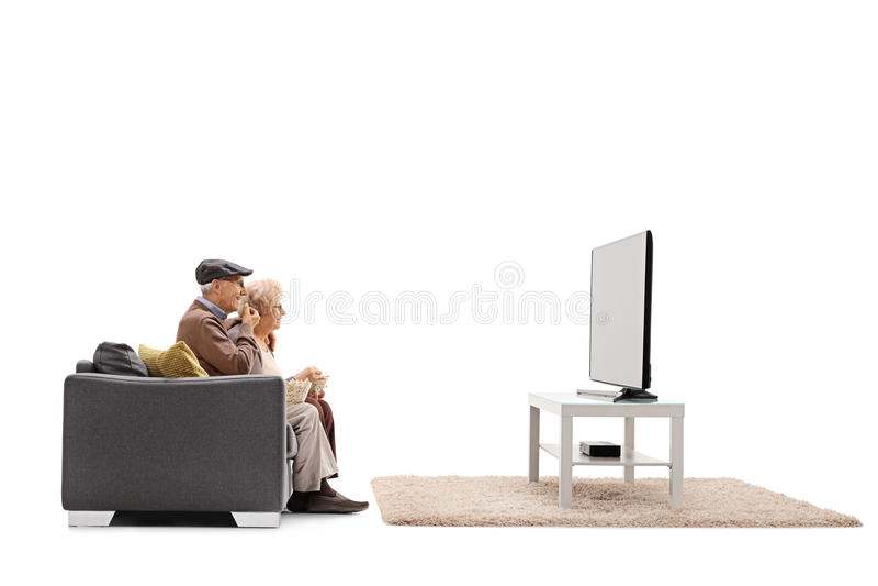 Aînés mangeant du maïs éclaté et regardant la télévision photos stock