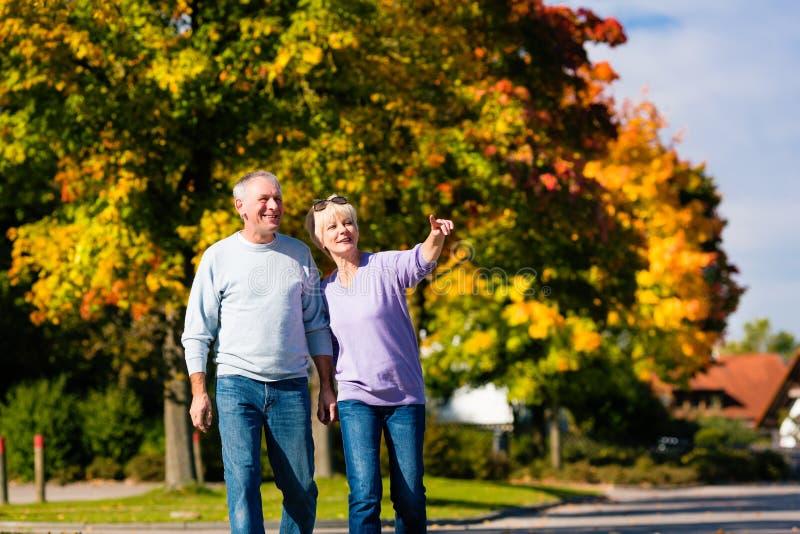 Aînés pendant l'automne ou l'automne marchant main dans la main photos stock