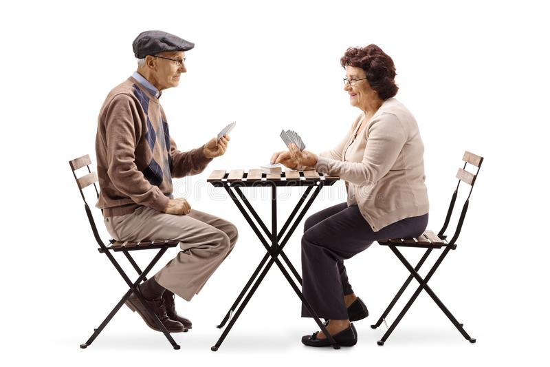 Aînés s'asseyant à une table et jouant des cartes photo libre de droits