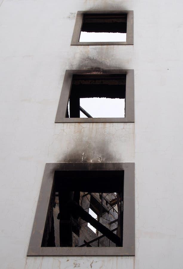 Aïe des fenêtres dans un bâtiment industriel grand abandonné par burn-out avec les poutres carbonisées et l'intérieur ruiné photos stock