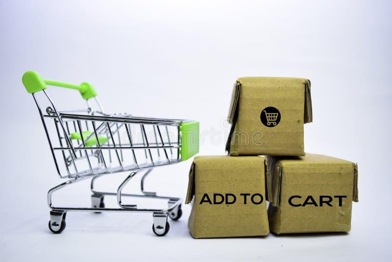 Añada al texto del carro en pequeñas cajas y carro de la compra Conceptos sobre compras en l?nea Aislado en el fondo blanco imagenes de archivo