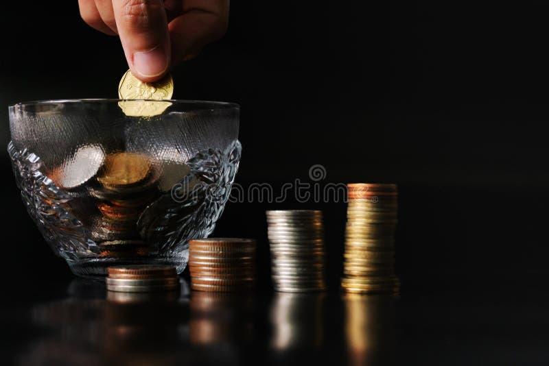 Añada la moneda del ahorro a la taza de la moneda, concepto del ahorro del dinero fotografía de archivo libre de regalías