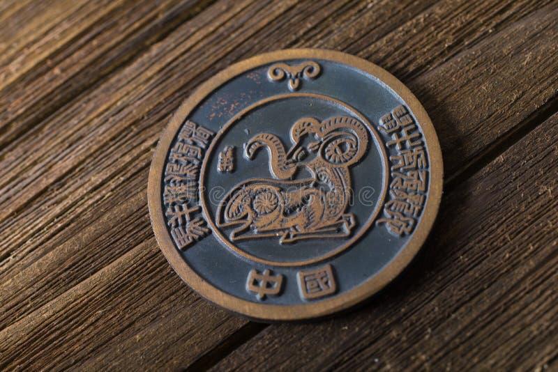 Año del Ram o de la cabra El zodiaco animal de la cabra firma adentro una moneda en la madera fotografía de archivo