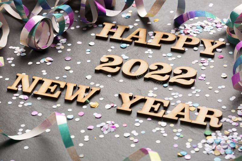 Año feliz 2022 - letras en madera Fondo negro foto de archivo