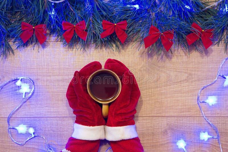 Año Nuevo/árbol de navidad con los arcos rojos, la guirnalda azul en la plantilla de madera del fondo y las manos en guantes rojo fotos de archivo libres de regalías