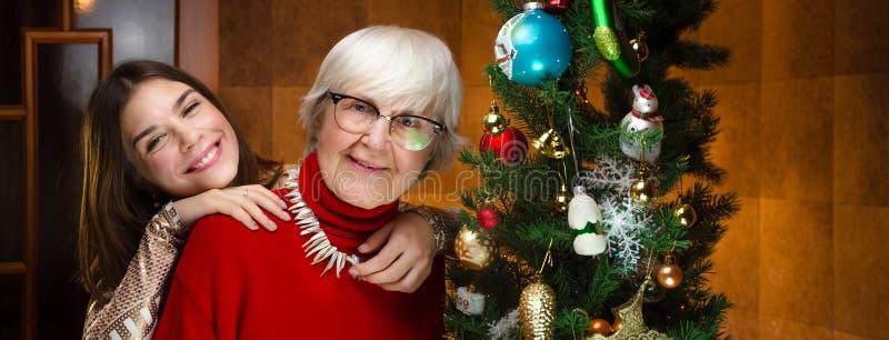 Año Nuevo abuela mayor y mujer caucásica joven, adolescente cerca del árbol de navidad la nieta, adolescencia que abraza, abraza imágenes de archivo libres de regalías