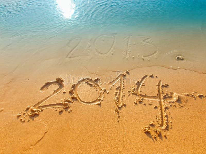 Año Nuevo 2014 concepto-escrito en arena en la playa imagenes de archivo
