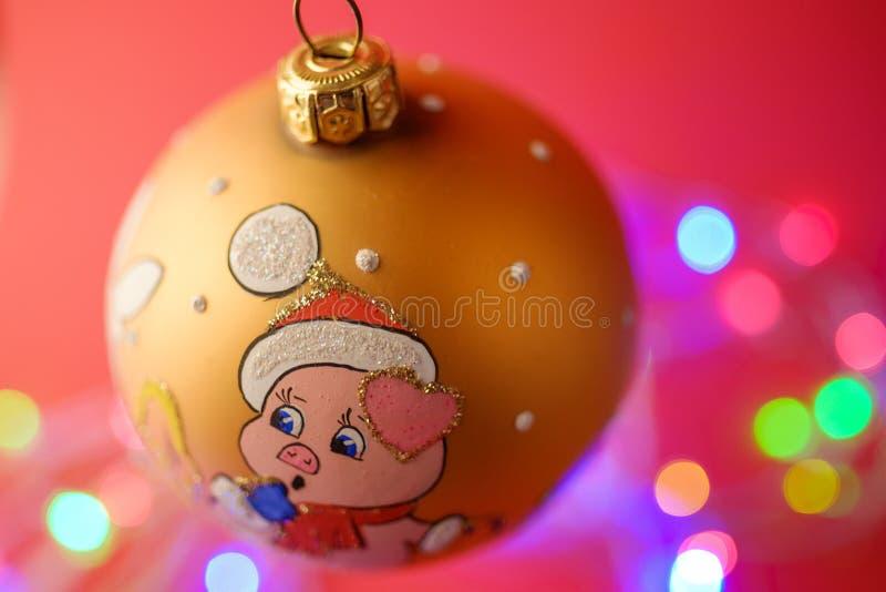 Año Nuevo de la bola de la Navidad con el fondo defocused del bokeh del cerdo en fondo rojo fotos de archivo
