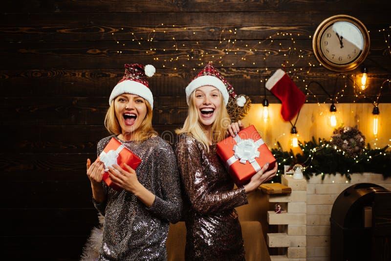 Año Nuevo de la celebración del encanto Caja de regalo rubia de la tenencia de la mujer de Papá Noel en la pared del vintage Retr fotos de archivo libres de regalías
