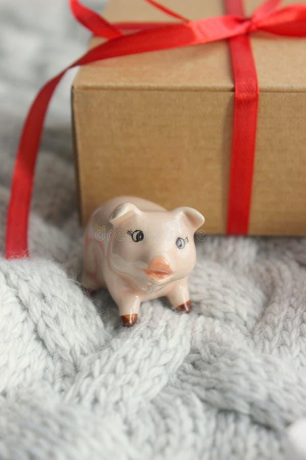Año Nuevo, el símbolo del año, la estatua de un cerdo en el fondo de una caja con los regalos, atado con una cinta roja imagen de archivo