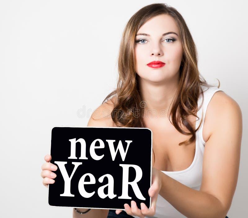 Año Nuevo escrito en la pantalla virtual mujer hermosa con los hombros desnudos que sostienen la tableta de la PC tecnología, Int imágenes de archivo libres de regalías