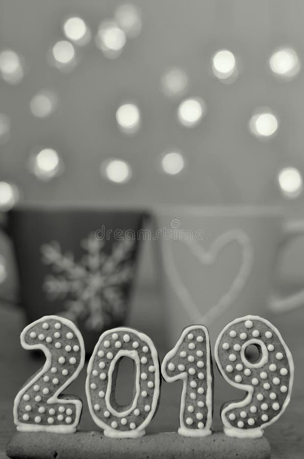 Año Nuevo 2019 Figuras del pan de jengibre en un tablero de madera Luces de la Navidad en el fondo Saludos del Año Nuevo Convenie fotografía de archivo libre de regalías