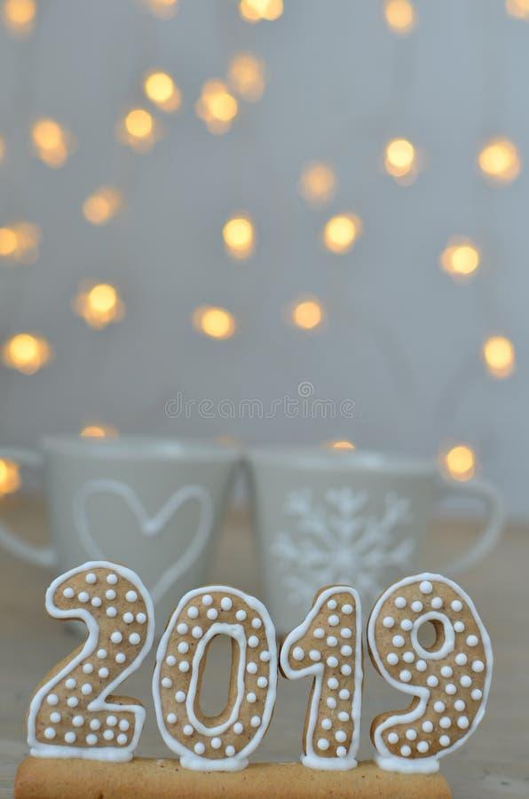 Año Nuevo 2019 Figuras del pan de jengibre en un tablero de madera Luces de la Navidad en el fondo Saludos del Año Nuevo Convenie fotos de archivo