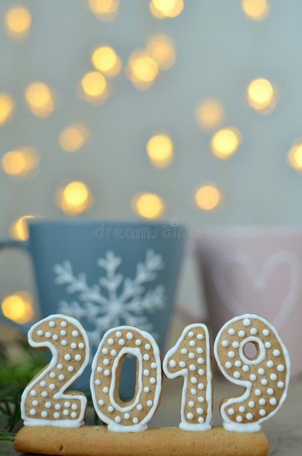 Año Nuevo 2019 Figuras del pan de jengibre en un tablero de madera Luces de la Navidad en el fondo Saludos del Año Nuevo Convenie foto de archivo