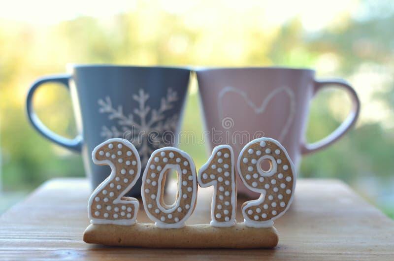 Año Nuevo 2019 Figuras del pan de jengibre en un tablero de madera Saludos del Año Nuevo Conveniente como fondo Dos tazas Junto e imagen de archivo libre de regalías