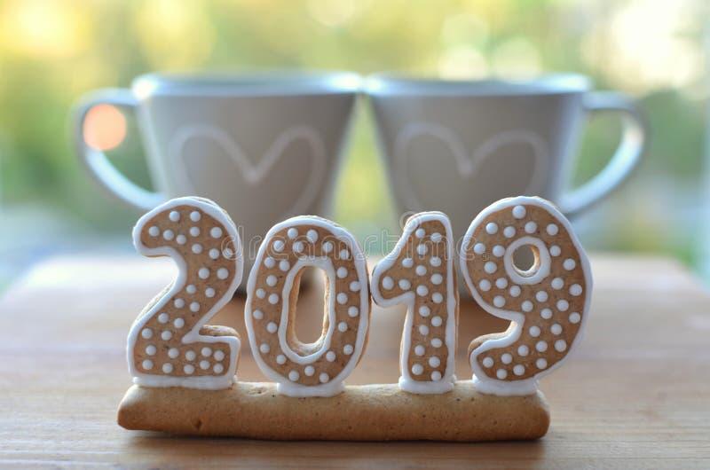 Año Nuevo 2019 Figuras del pan de jengibre en un tablero de madera Saludos del Año Nuevo Conveniente como fondo Dos tazas Junto e imagen de archivo