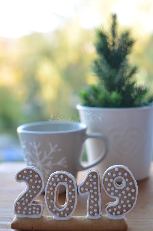 Año Nuevo 2019 Figuras del pan de jengibre en un tablero de madera Saludos del Año Nuevo Conveniente como fondo Dos tazas Junto e foto de archivo