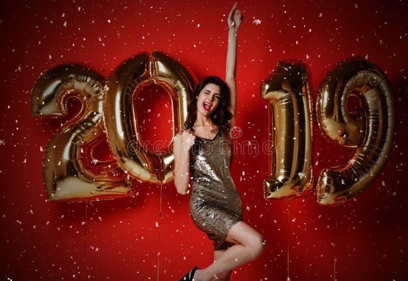 Año Nuevo Mujer con los globos que celebra en el partido imagenes de archivo