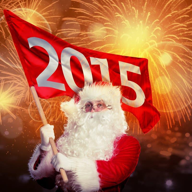 Año Nuevo que viene por Santa Claus Papá Noel con la bandera 2015 en fuego artificial foto de archivo