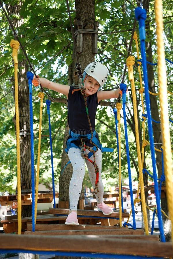 8 años de la muchacha en parque de la aventura del bosque Subida del niño en alto rastro de la cuerda Patio al aire libre con man imagenes de archivo