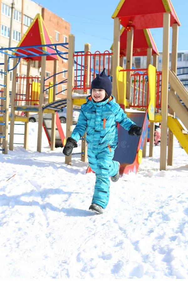 5 años de niño pequeño en guardapolvo caliente corren al aire libre en invierno fotografía de archivo