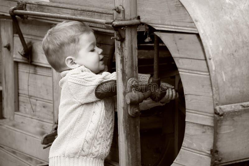 2 años del bebé curioso que maneja con la vieja AGR fotografía de archivo libre de regalías