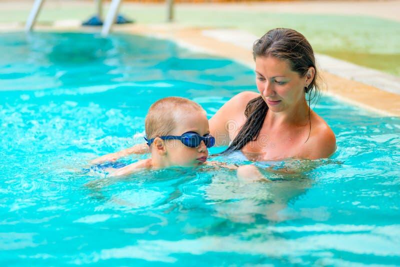 5 años del muchacho que aprende nadar foto de archivo